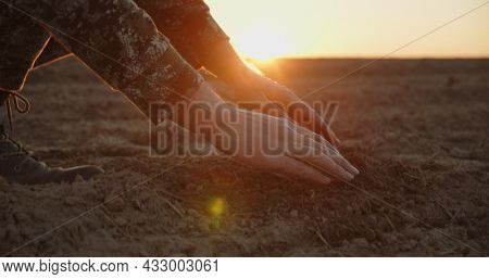 Farmer holding ground in hands closeup while sunset. Male hands touching soil on the field during sunset. Farmer is checking soil quality before sowing. Side view.
