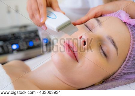 Woman in a spa salon on cosmetic procedures for facial care. Cosmetologist making a woman a therapeutic procedure on a face. Beautician makes medical procedures using a professional  equipment.