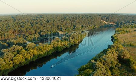 Aerial view above a beautiful landscape with a  river while sunset. Aerial view from drone flies over a beautiful summer landscape.