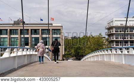 Le Havre, France - August 8, 2021: Two Migrant Women Crossing The Footbridge Across Commerce Basin I