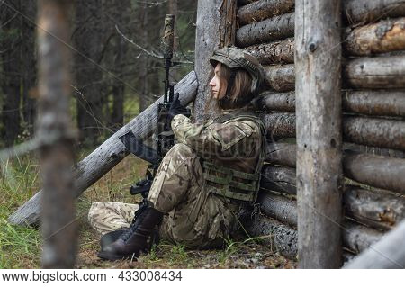 A Sad And Tired Girl In A Military Uniform Is Sitting On The Ground Leaning Against The Wooden Wall