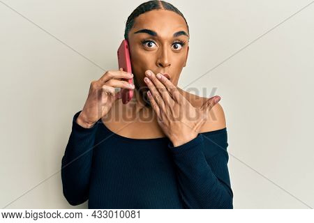 Hispanic transgender man wearing make up and long hair having conversation talking on the smartphone covering mouth with hand, shocked and afraid for mistake. surprised expression