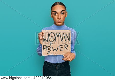 Hispanic transgender man wearing make up and long hair holding we need a change banner thinking attitude and sober expression looking self confident