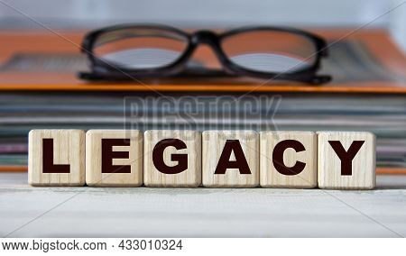 Legacy - Word On Wooden Cubes On The Background Of A Folder With Documents And Glasses