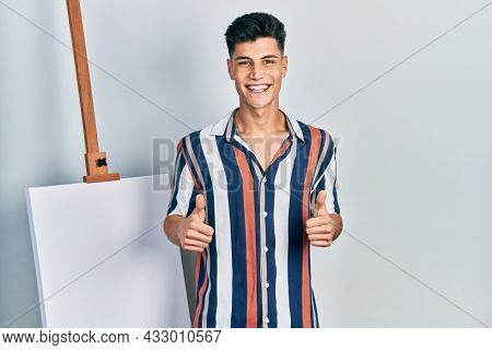 Young hispanic man standing close to empty canvas success sign doing positive gesture with hand, thumbs up smiling and happy. cheerful expression and winner gesture.