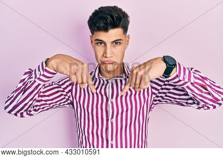 Young hispanic man wearing casual clothes pointing down looking sad and upset, indicating direction with fingers, unhappy and depressed.