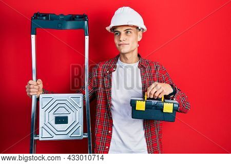 Young hispanic man holding tools box wearing hardhat by construction stairs smiling looking to the side and staring away thinking.