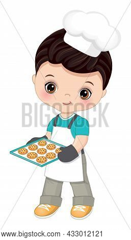 Cute Little Boy Wearing Chefs Toque, Oven And Apron Holding Baking Tray With Cookies. Cute Boy Is Da