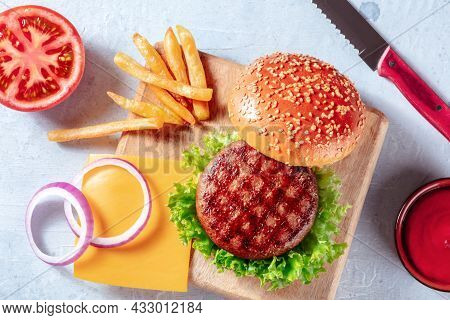 Burger Ingredients, Overhead Flat Lay Shot With French Fries And A Barbecue Sauce. Hamburger And Pot