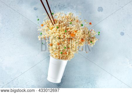 Ramen Cup With Instant Noodles Flying Out Of It And Chopsticks, Fast Food Levitation. Noodle Meal Wi