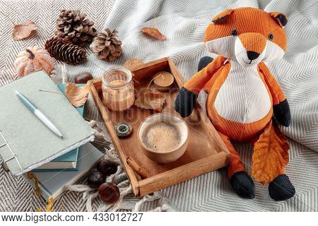 Hygge Still Life With A Toy Fox, A Cup Of Coffee, Autumn Leaves And A Journal On A Warm Blanket