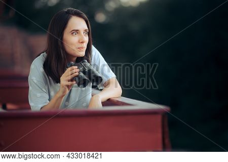 Curious Woman Holding A Pair Of Binocular Spying On Her Neighbors
