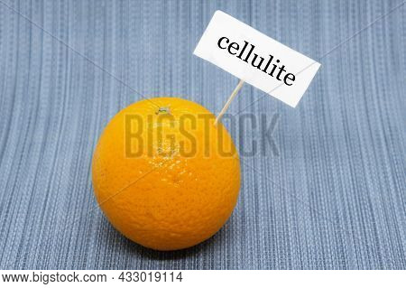 Orange With A Sign Stuck In It That Says Cellulite. Orange Peel As A Symbol Of Cellulite On The Skin