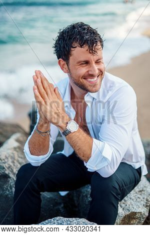 Happy Masculine Male In Stylish White Shirt And With Wet Hair Sitting On Rock At Seaside And Looking