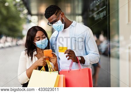 Afro Couple In Masks Using Smartphone Holding Debit Credit Card