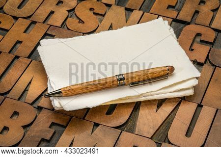 small sheet of a blank white Khadi rag paper with a stylish pen against letterpress wood type