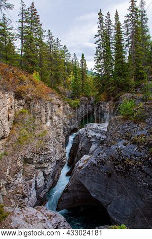 Maligne Canyon is gorge in the Canadian Rockies. Travel to the Rocky Mountains. Cool cloudy day. The sheer canyon walls and the seething icy water below