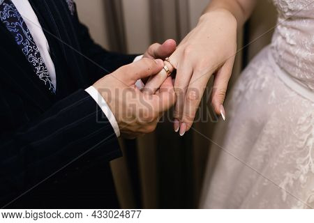 The Groom Puts A Gold Wedding Ring On The Bride's Finger Close-up. The Man Groom Gently Holds The Br