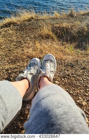 Female Feet Seen From Above. Foot And Legs In In Green Sports Sneakers. Girl Sitting On A Hill Overl