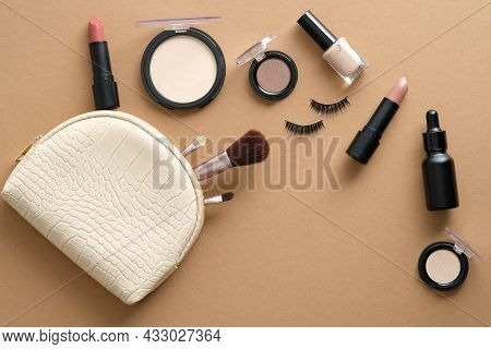 Makeup Bag With Cosmetic Products Spilling Out On To Brown Table. Stylish Make Up Artist Pouch With