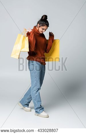 Full Length Of Pleased Woman In Sweater And Jeans Holding Yellow Shopping Bags On Grey