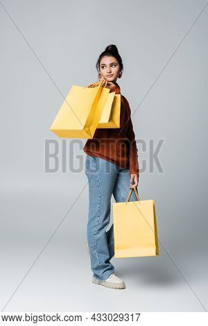 Full Length Of Young Shopaholic In Sweater And Jeans Holding Yellow Shopping Bags On Grey