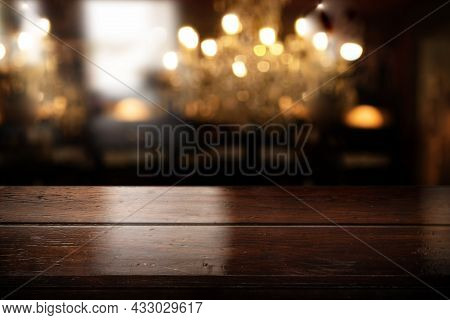 Empty Wooden Bar Counter With Blurred Restaurant Interior And Elegant Bokeh. Background For Gastrono