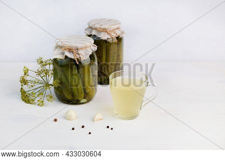Pickled Cucumbers In Cans, Homemade Canning. Pickled Juice Or Cucumber Pickle On A White Wooden Back