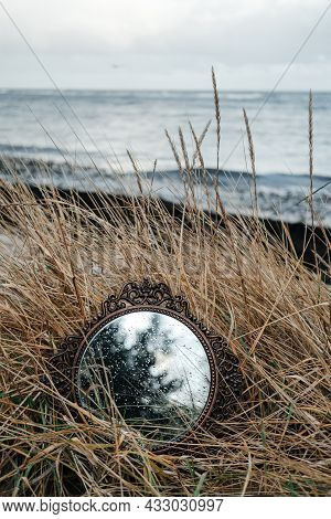 Vintage Mirror On Seaside Reflects Forest And Sky.