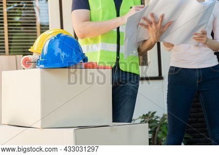 Asian Professional Architect Holding Blueprint And Explain About The Plan With Homeowner For House R