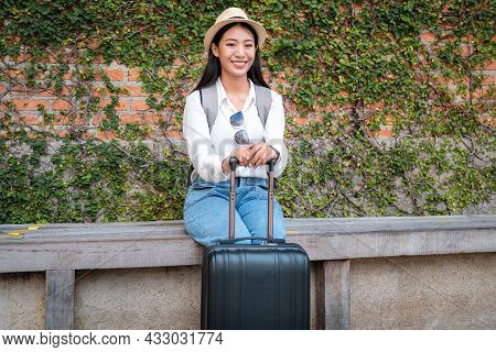 Asian Woman Tourist Sitting On The Chair With Hat And Holding Her Luggage To Preparing On Holiday Tr