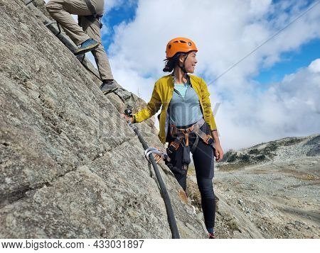 Via Ferrata hiking climbing on the top of Whistler Peak. Guided tour group activity for tourists travel in British Columbia, BC, Canada vacation. Asian woman hiker happy.