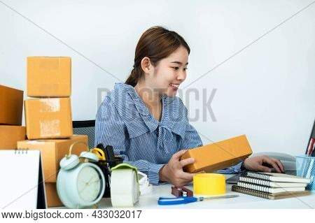 Asian Woman Small Business Owner Holding Box Of Parcel In Hands And Checking Order On Laptop While C