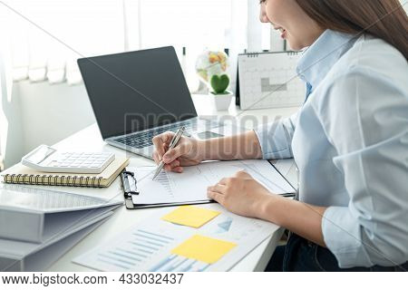 Woman Office Worker Sitting To Working And Writing Business Project Report On Clipboard During Check