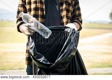 Close Up Of Volunteer Man In Gloves To Picking Up Plastic Bottle Into Plastic Black Bag For Cleaning