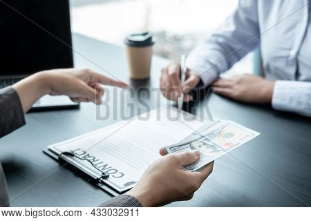 Man Employee Giving Bribe Money To Business Woman And Pointing At The Contract Signing Box While She
