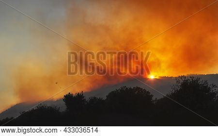 Wildfire On A Mountain Slope At Sunset With Dramatic Red Sky, Heavy Smoke And Silhouette Of Helicopt