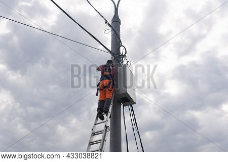 Perm, Russia - August 25, 2021: Electrician Or Telecommunications Lineman Works On Laying A Cable At