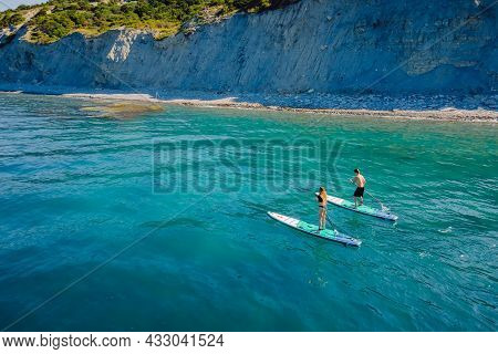 May 28, 2021. Anapa, Russia. Couple Of Athletic Traveling On Stand Up Paddle Board At Quiet Sea. Peo
