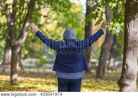 Happy Woman With Arms Outstretched In Autumn Park. Happiness And Positivity Concept.