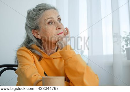 Beautiful Old Grandmother With Grey Hair And Face With Wrinkles Is Thinking About Something On Windo