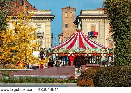 ALBA, ITALY - OCTOBER 24, 2020: Carrousel on the town square among trees with yellow leaves during famous annual White Truffles Festival in small town of Alba in Piedmont, Northern Italy .