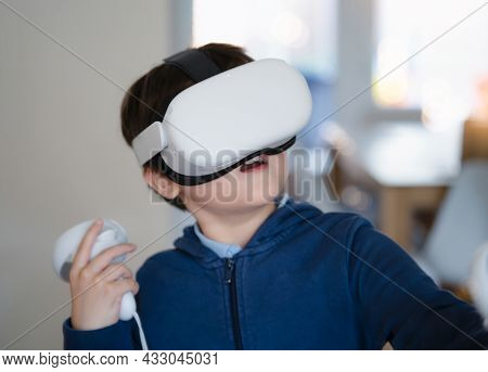 Amazed Young Kid Wearing Virtual Reality Goggles. Emotional Boy Playing Video Games Looking In Vr He