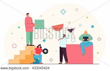 Team Of People Organizing Geometric Figures Of Different Shapes. Group Of Men And Women Holding Tria