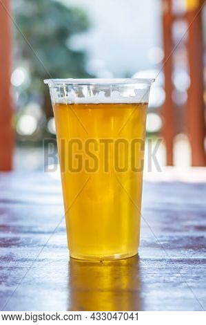 Beer In A Plastic Mug On A Brown Table With A Blurry Background