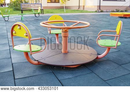 Empty сhildrens Metal Carousel On Outdoor Playground. Concept Of Entertaining Street Leisure For Chi