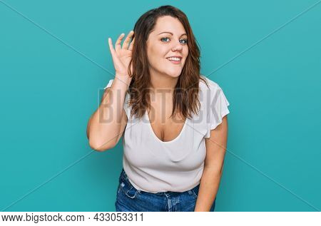 Young plus size woman wearing casual white t shirt smiling with hand over ear listening an hearing to rumor or gossip. deafness concept.