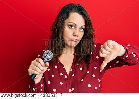 Young caucasian woman singing song using microphone with angry face, negative sign showing dislike with thumbs down, rejection concept