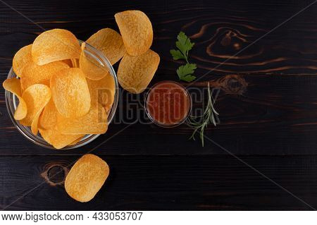 Potato Chips And Sauce On Wooden Background, Top View With Copy Space.