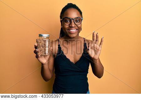 African american woman with braided hair holding lentils doing ok sign with fingers, smiling friendly gesturing excellent symbol